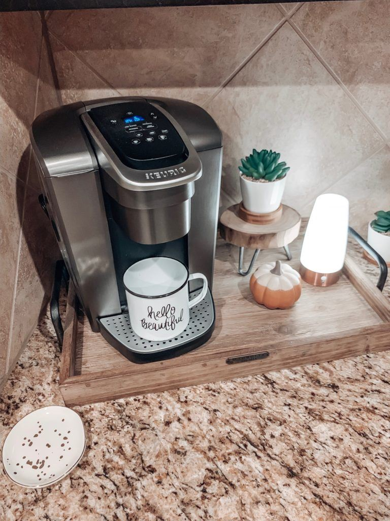 Keurig Elite with 'Hello Beautiful' campfire mug from Amazon. Motion sensor light with faux succulents on a wood slice stand and ceramic pumpkin