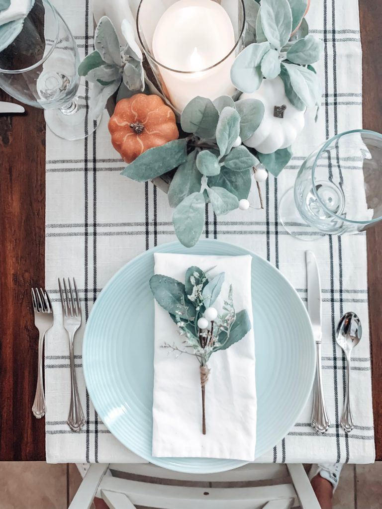 table settings on dining room table plus center piece with faux pumpkins and lambs ear in wooden bowl
